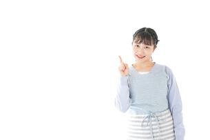 笑顔で指差す若い主婦の写真素材 [FYI04717427]