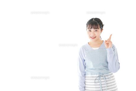 笑顔で指差す若い主婦の写真素材 [FYI04717433]