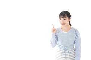 笑顔で指差す若い主婦の写真素材 [FYI04717437]