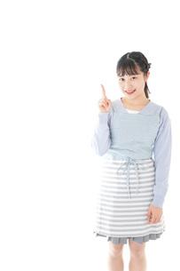 笑顔で指差す若い主婦の写真素材 [FYI04717438]