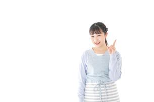 笑顔で指差す若い主婦の写真素材 [FYI04717441]