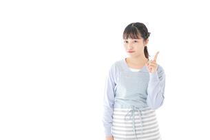 笑顔で指差す若い主婦の写真素材 [FYI04717447]