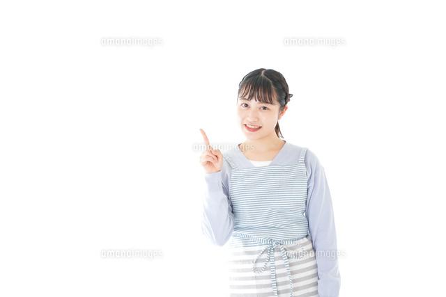 笑顔で指差す若い主婦の写真素材 [FYI04717453]