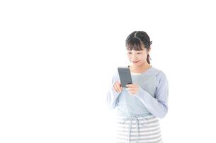 笑顔でスマートフォンを使う若い主婦の写真素材 [FYI04717463]