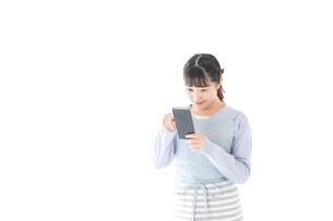 笑顔でスマートフォンを使う若い主婦の写真素材 [FYI04717466]