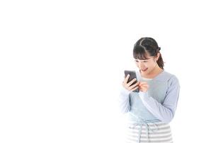 笑顔でスマートフォンを使う若い主婦の写真素材 [FYI04717467]
