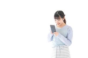 笑顔でスマートフォンを使う若い主婦の写真素材 [FYI04717468]