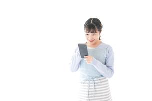 笑顔でスマートフォンを使う若い主婦の写真素材 [FYI04717471]