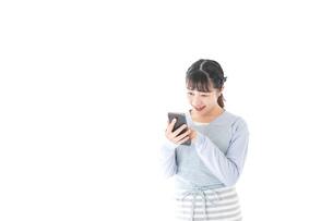 笑顔でスマートフォンを使う若い主婦の写真素材 [FYI04717472]