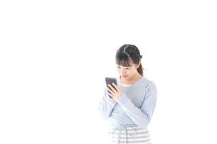 笑顔でスマートフォンを使う若い主婦の写真素材 [FYI04717474]