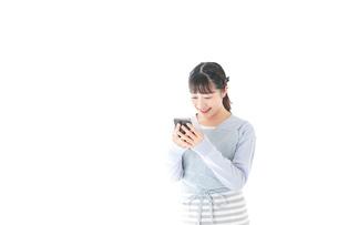 笑顔でスマートフォンを使う若い主婦の写真素材 [FYI04717476]
