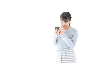 笑顔でスマートフォンを使う若い主婦の写真素材 [FYI04717479]