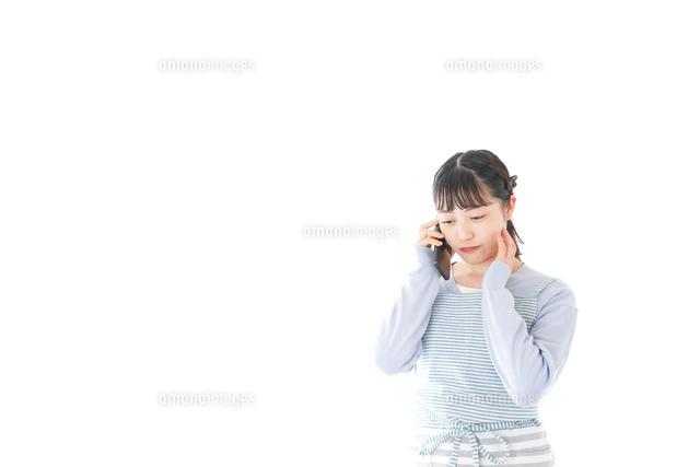 笑顔でスマートフォンを使う若い主婦の写真素材 [FYI04717481]