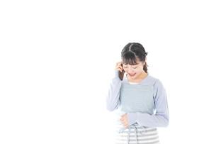 笑顔でスマートフォンを使う若い主婦の写真素材 [FYI04717482]