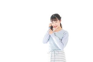 笑顔でスマートフォンを使う若い主婦の写真素材 [FYI04717485]