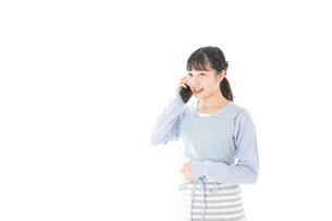 笑顔でスマートフォンを使う若い主婦の写真素材 [FYI04717487]