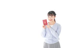 パスポートを持つ若い女性の写真素材 [FYI04717606]