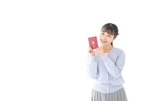 パスポートを持つ若い女性の写真素材 [FYI04717607]