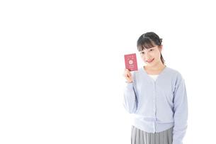 パスポートを持つ若い女性の写真素材 [FYI04717611]