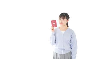 パスポートを持つ若い女性の写真素材 [FYI04717612]