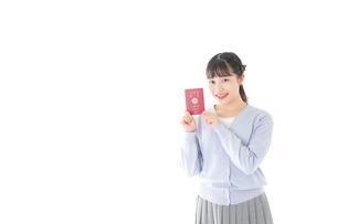 パスポートを持つ若い女性の写真素材 [FYI04717615]