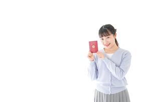 パスポートを持つ若い女性の写真素材 [FYI04717618]