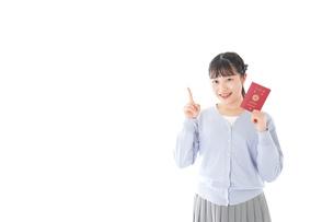 パスポートを持つ若い女性の写真素材 [FYI04717620]