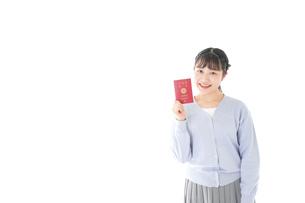 パスポートを持つ若い女性の写真素材 [FYI04717621]
