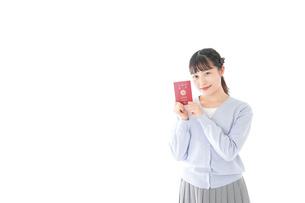 パスポートを持つ若い女性の写真素材 [FYI04717622]