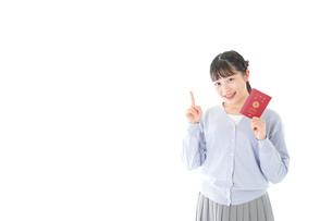 パスポートを持つ若い女性の写真素材 [FYI04717625]