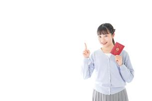 パスポートを持つ若い女性の写真素材 [FYI04717628]