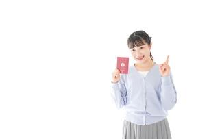 パスポートを持つ若い女性の写真素材 [FYI04717629]
