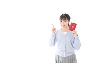 パスポートを持つ若い女性の写真素材 [FYI04717631]