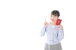 パスポートを持つ若い女性の写真素材 [FYI04717632]