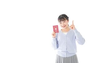 パスポートを持つ若い女性の写真素材 [FYI04717633]