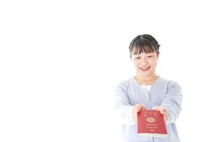 パスポートを持つ若い女性の写真素材 [FYI04717635]