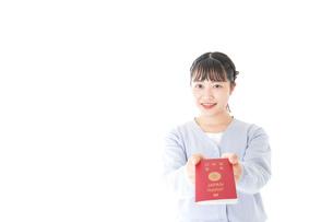 パスポートを持つ若い女性の写真素材 [FYI04717636]