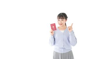 パスポートを持つ若い女性の写真素材 [FYI04717637]