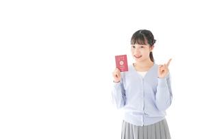 パスポートを持つ若い女性の写真素材 [FYI04717638]