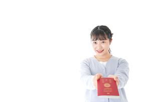 パスポートを持つ若い女性の写真素材 [FYI04717639]
