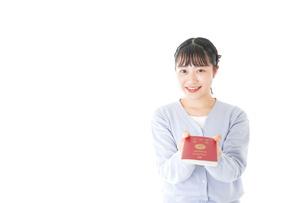 パスポートを持つ若い女性の写真素材 [FYI04717640]