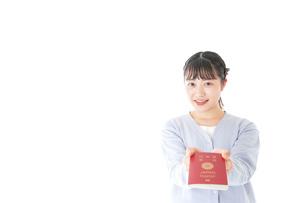 パスポートを持つ若い女性の写真素材 [FYI04717647]