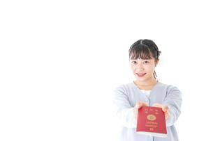 パスポートを持つ若い女性の写真素材 [FYI04717648]