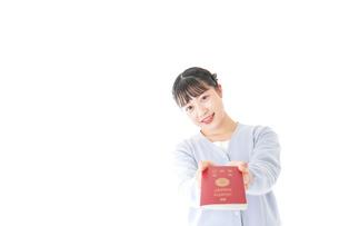 パスポートを持つ若い女性の写真素材 [FYI04717661]
