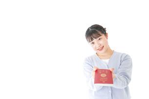 パスポートを持つ若い女性の写真素材 [FYI04717662]