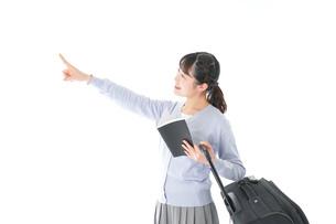 ガイドブックを持ち一人旅をする若い女性の写真素材 [FYI04717691]