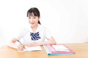 制服姿で勉強をする若い学生の写真素材 [FYI04717772]