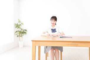制服姿で勉強をする若い学生の写真素材 [FYI04717774]