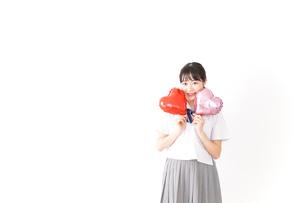 ハートマークを持つ若い女性の写真素材 [FYI04717799]