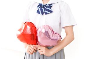 ハートマークを持つ若い女性の写真素材 [FYI04717812]